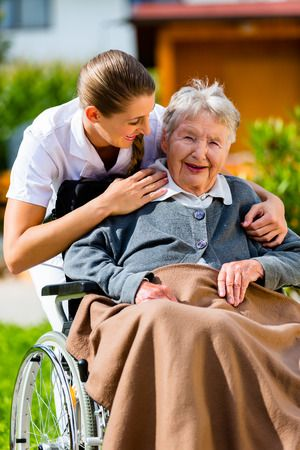 37893893 - senior woman in nursing home with nurse in garden sitting in wheelchair