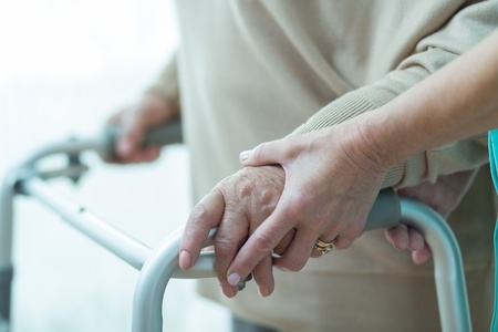 48725599 - close-up of woman using walker assisted by carer